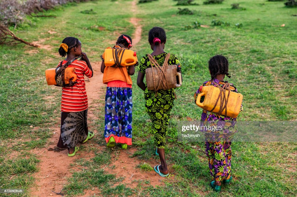 African girls carrying water from the well, Ethiopia, Africa : Stock Photo
