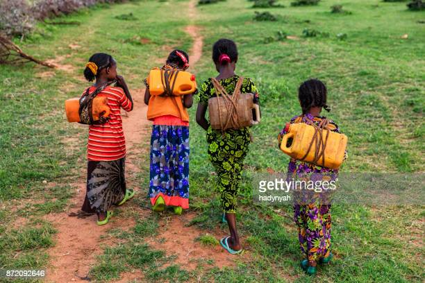 African girls carrying water from the well, Ethiopia, Africa