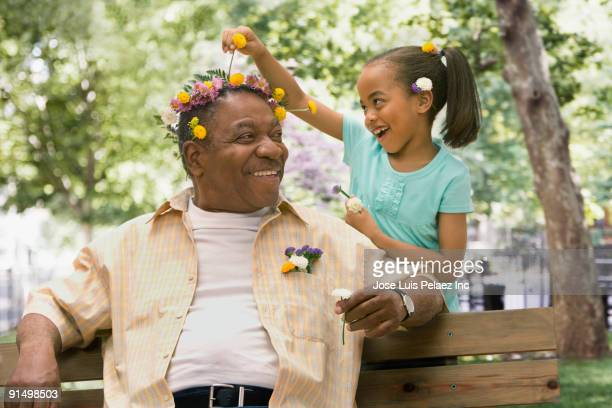 african granddaughter decorating grandfather's head with flowers - generation gap stock pictures, royalty-free photos & images