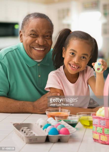 African grandfather and granddaughter coloring Easter eggs