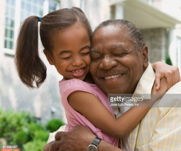 African grandfather and granddaughter hugging with eyes closed