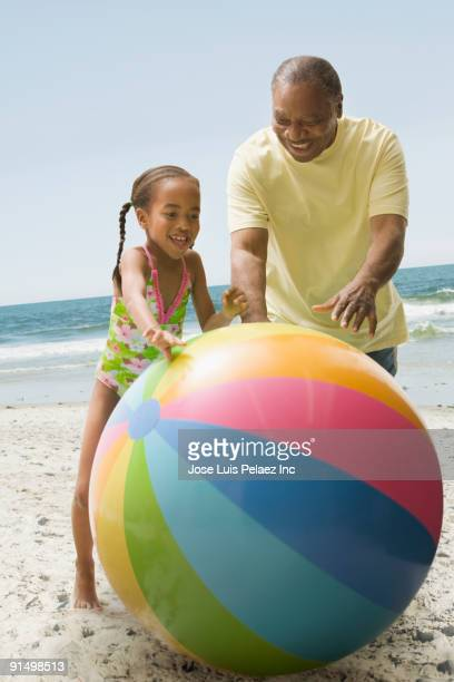 african grandfather and granddaughter playing on beach with large ball - man with big balls stock photos and pictures