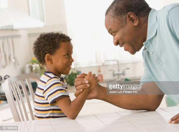 African grandfather and grandson arm wrestling