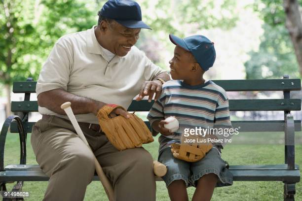 african grandfather and grandson holding baseball equipment on park bench - baseball sport stock pictures, royalty-free photos & images