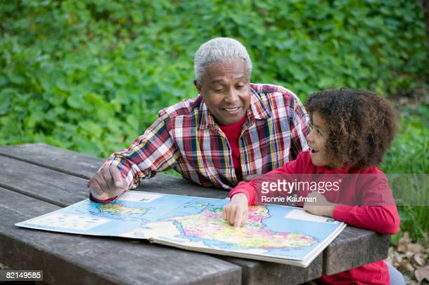 African grandfather and grandson looking at map