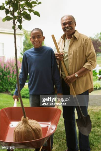 african grandfather and grandson planting tree - generation gap stock pictures, royalty-free photos & images
