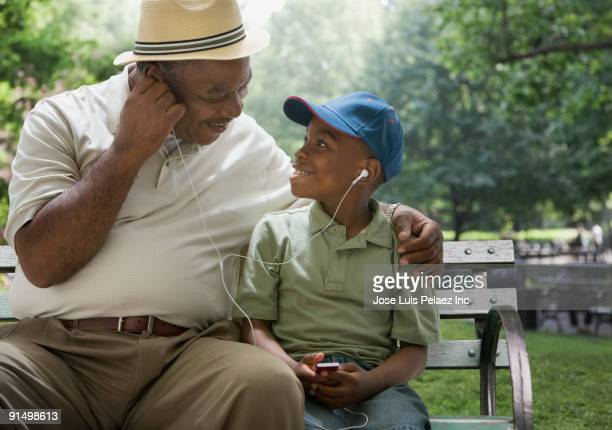 African grandfather and grandson sharing headphones on park bench