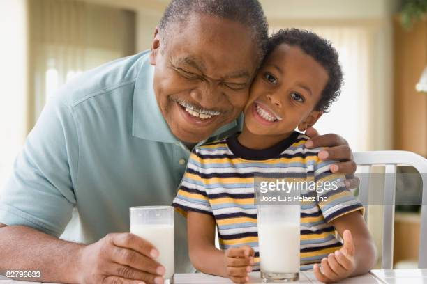 African grandfather and grandson with milk mustaches