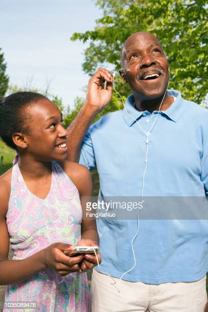 African grandfather listening to granddaughter's mp3 player