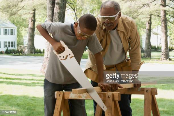 african grandfather watching grandson saw wood - generation gap stock pictures, royalty-free photos & images