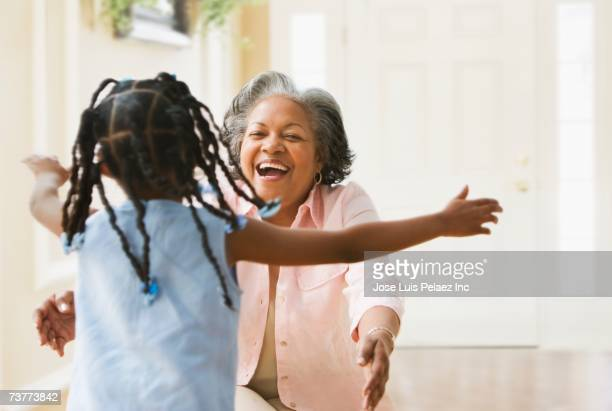 african grandmother and granddaughter running to hug each other - grandmother stock pictures, royalty-free photos & images