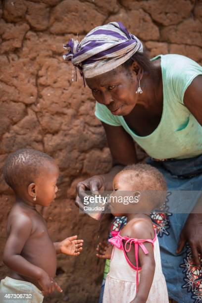 African grandmother gives water to children