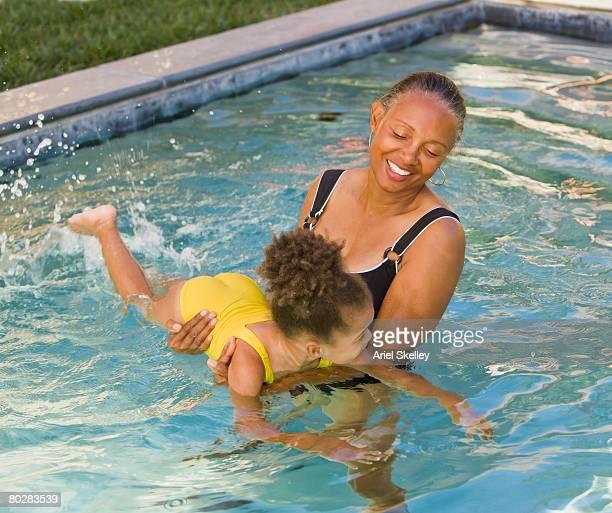 African grandmother helping granddaughter to swim