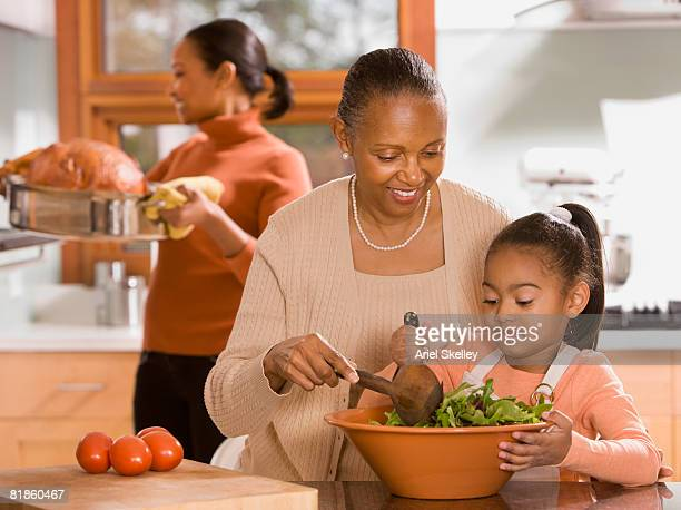 african grandmother, mother and daughter preparing food - black family dinner stock photos and pictures