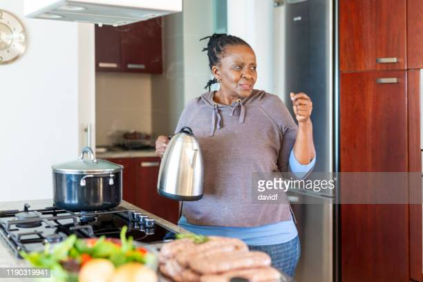 african grandmother with a kettle in the kitchen - kettle stock pictures, royalty-free photos & images