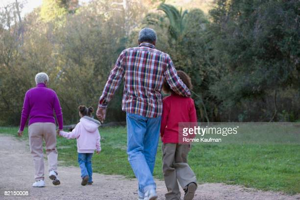African grandparents and grandchildren walking on path