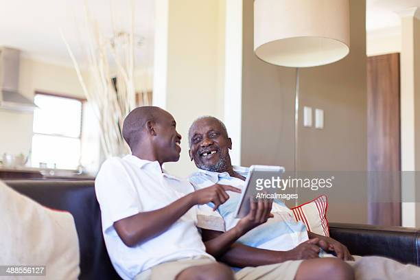African grandson showing his grandfather a new game.