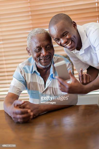 African grandson teaching his grandfather how to use a cellphone