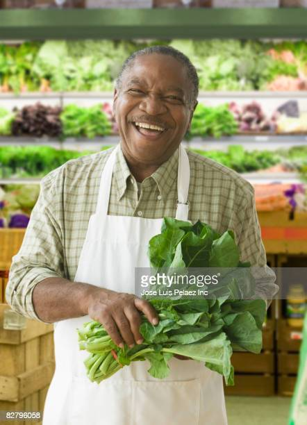 african grocer holding lettuce - sales clerk stock pictures, royalty-free photos & images