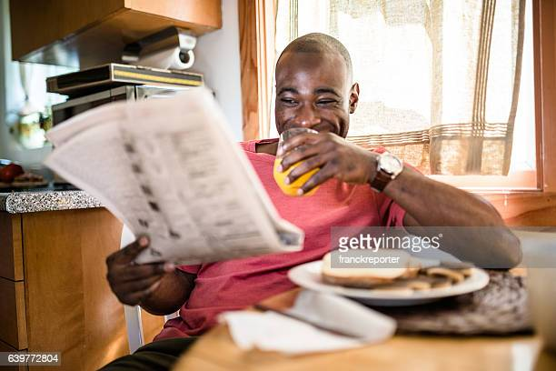 african guy doing breakfast and reading the newspaper