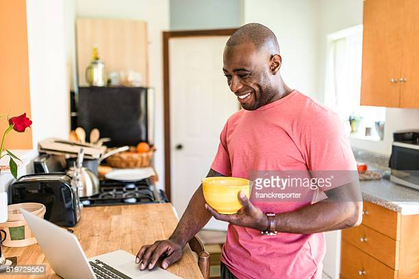 african guy doing the breakfast on the pc