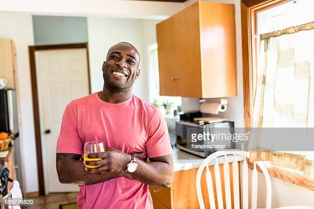 african guy smiling drinking orange juice