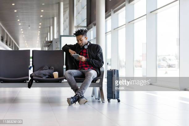 african guy waiting for boarding flight - bench stock pictures, royalty-free photos & images