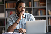 African guy wearing headset learn foreign language using internet websites