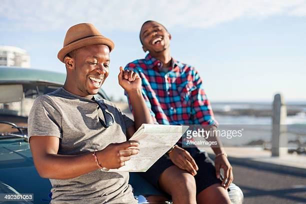 African hipster friends reading a map on holiday