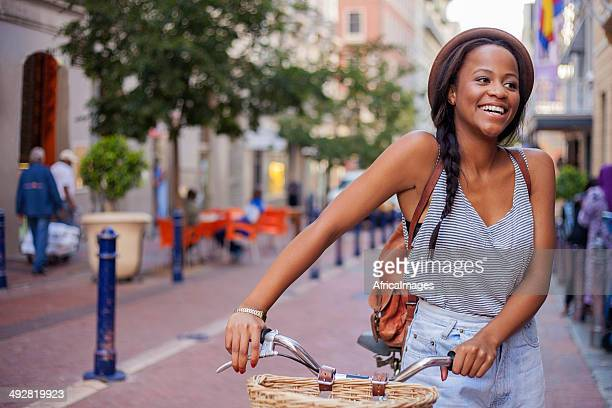 African hipster girl walks down the street with her bike