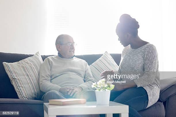 Afrikanischer Hause Pflegekraft Gespräch mit alter Mann zu Hause