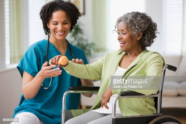 african home nurse helping woman in wheelchair with hand weight - human limb stock pictures, royalty-free photos & images