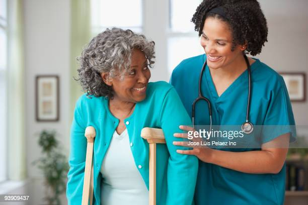 african home nurse helping woman on crutches - patient safety stock pictures, royalty-free photos & images