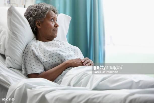 african hospital patient looking out window - old woman in sick bed stock photos and pictures
