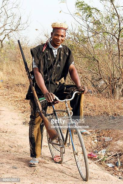 African hunter riding bicycle