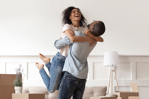 African husband lifting happy wife celebrating moving day with boxes 1158481668