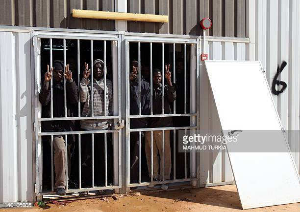 African immigrants flash the Vsign from inside a block at the makeshift detention centre in the mountainous city of Gheryan southwest of the captial...