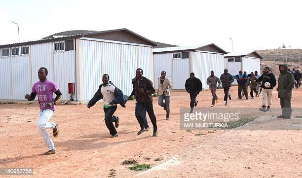 African immigrants run for exercise at the makeshift detention centre in the mountainous city of Gheryan southwest of the captial Tripoli on February...