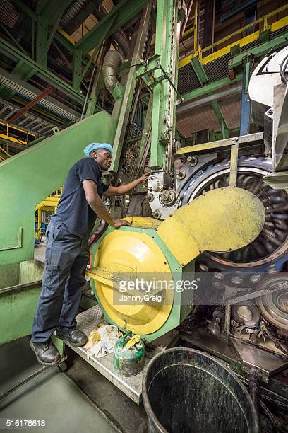 African industrial worker inspecting machine in aluminium processing plant