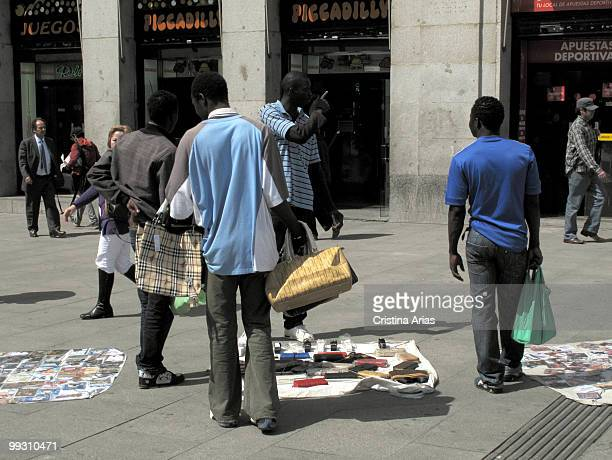 African inmigrants selling illegally falsified products of prestigious brands handbags purses belts CD music DVD sunglasses etc in the city center...