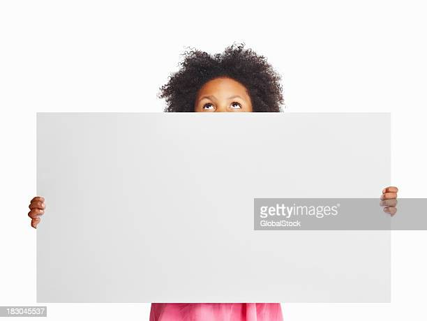 African kid looking up as she holds a billboard