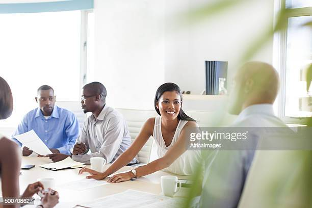 African lady smiles during a boardroom meeting