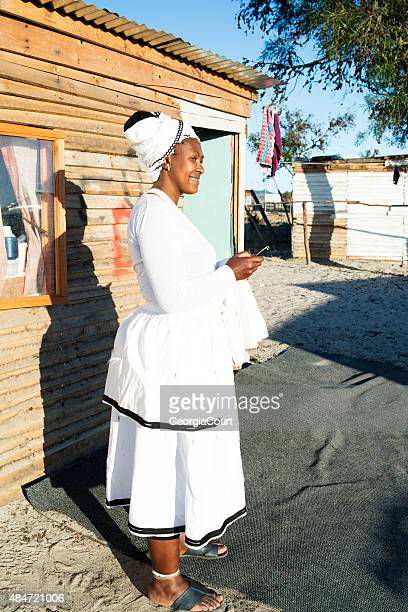 african lady texting on her phone - sangoma stock photos and pictures