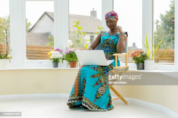 african lady working on her laptop - sleeveless dress stock pictures, royalty-free photos & images
