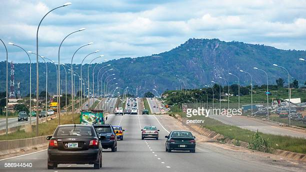 african landscape and highway traffic. abuja, nigeria. - abuja stock pictures, royalty-free photos & images