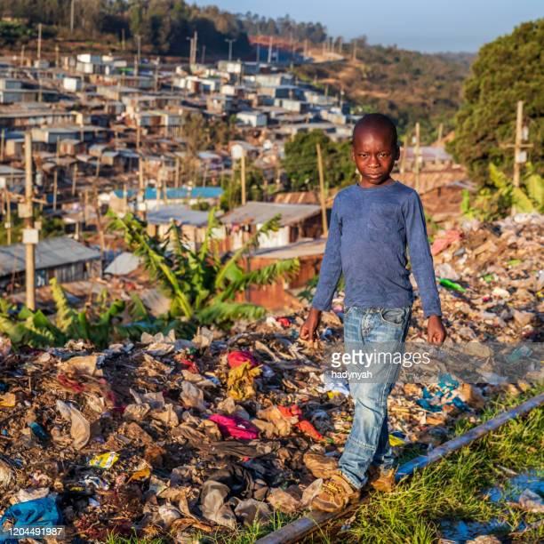 afrikanischer kleiner junge zu fuß auf bahngleisen, kibera slum im hintergrund, kenia, ostafrika - kenia stock-fotos und bilder