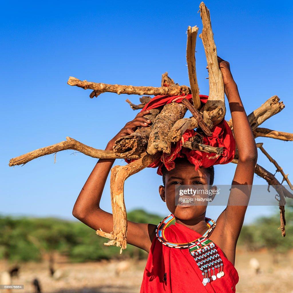 African little girl carrying brushwood on savanna, Kenya, East Africa : Stock Photo
