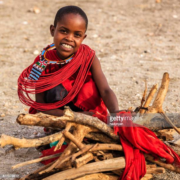 african little girl carrying brushwood on savanna, kenya, east africa - eastern african tribal culture stock photos and pictures