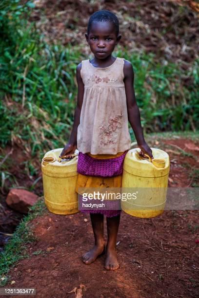 井戸から水を運ぶアフリカの小さな女の子, ケニア, 東アフリカ - 児童就労 ストックフォトと画像