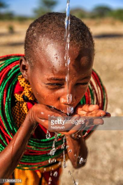 african little girl from samburu tribe drinking fresh water on savanna., east africa - african tribal culture stock pictures, royalty-free photos & images
